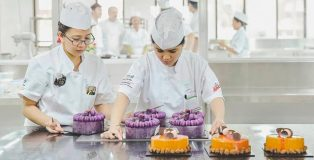 Students at the academy of pastry arts assembling cakes