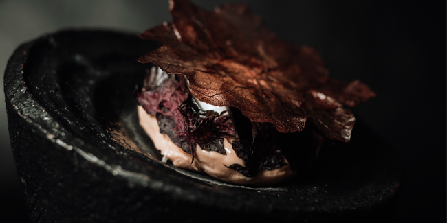 Frozen guava, sea water meringue and black olive plated dessert by Will Aghajanian